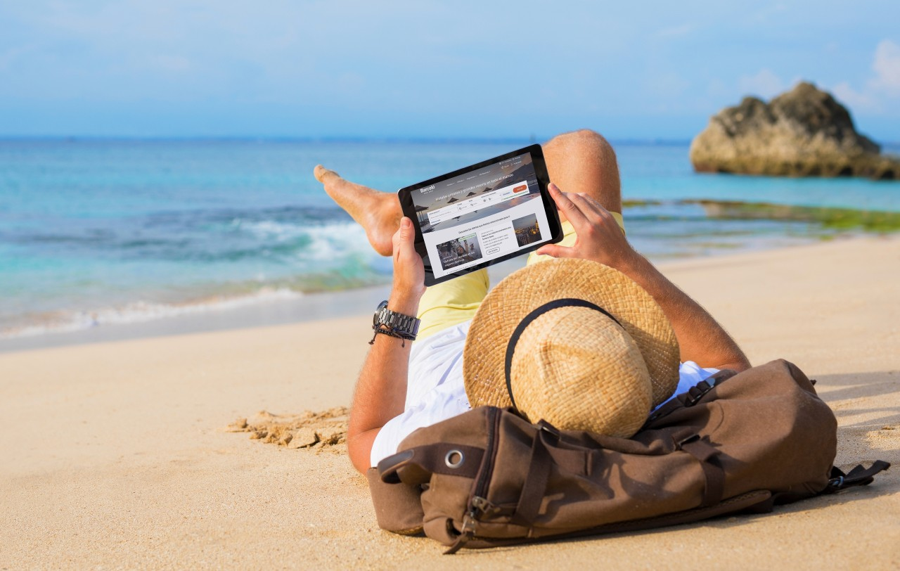 Unrecognizable male buying airline tickets online on tablet while relaxing on beach.