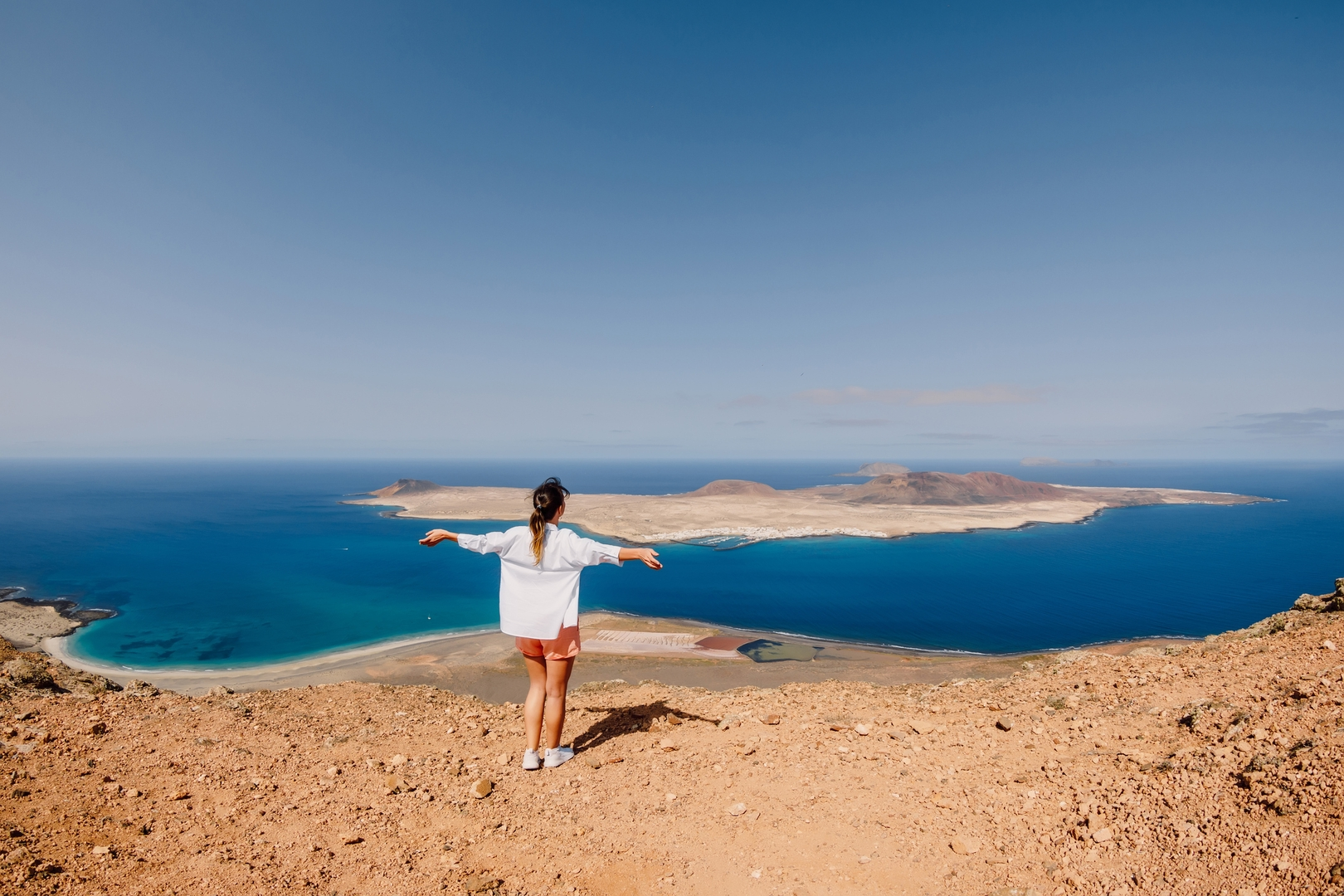 Happy traveller woman and scenic viewpoint to La Graciosa from Lanzarote island