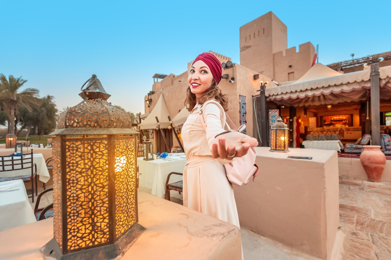 Follow happy woman traveler wearing dress and turban walking through the streets of an old Arab town or village in the middle of the desert. Concept of tourism and adventure alone