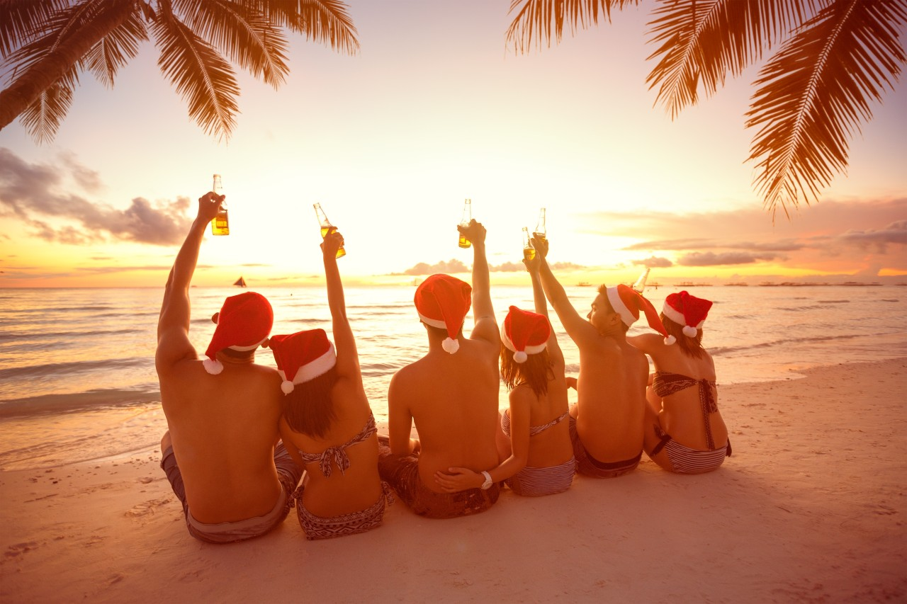 Back view of group people with raised hands holding a bottle of beer on beach, Christmas holiday