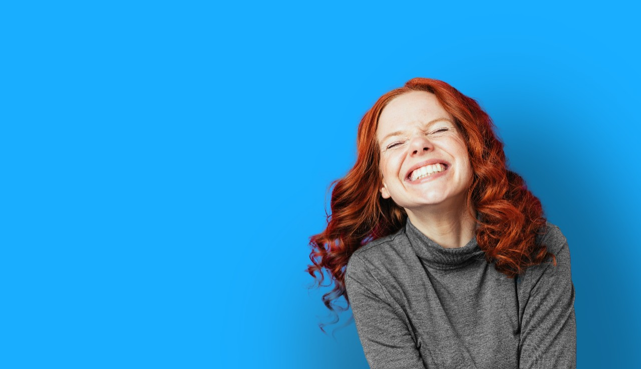 Portrait of young red-haired laughing woman against pink background with copy space