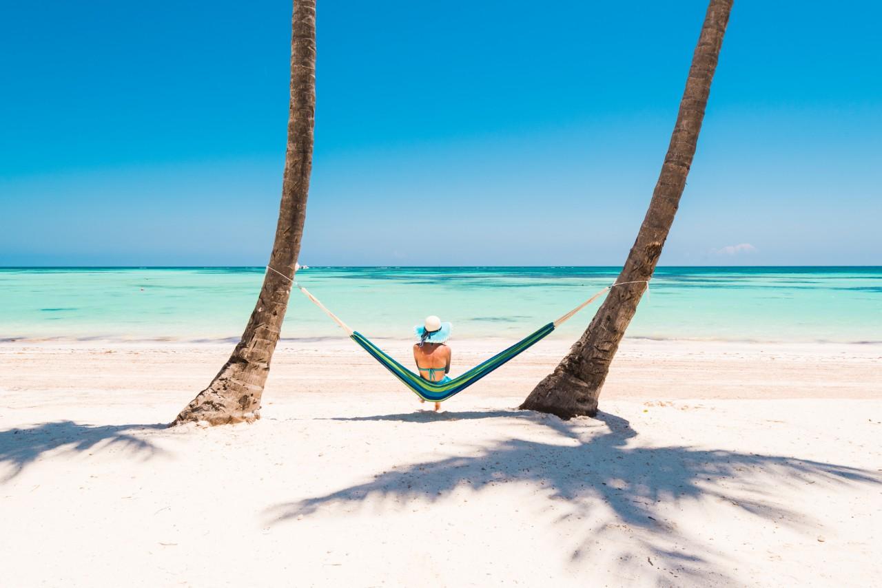 Juanillo Beach (playa Juanillo), Punta Cana, Dominican Republic. Woman relaxing on a hammock on a palm-fringed beach.