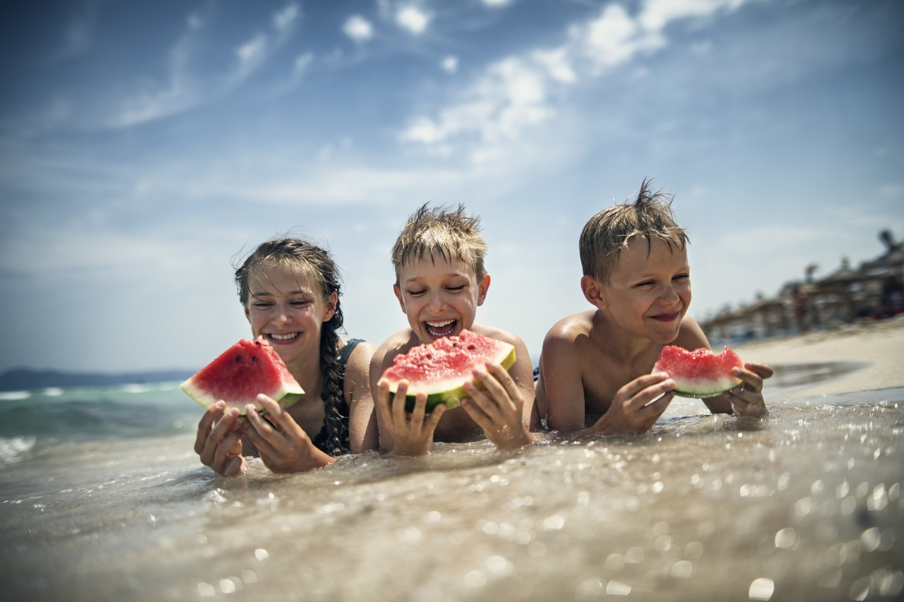 Brothers and sister eating watermelon on the beach on a sunny summer day.Nikon D850