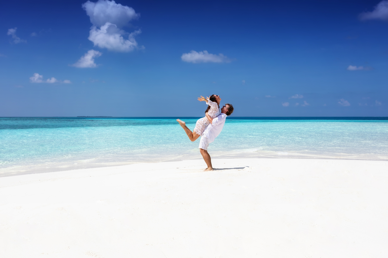 Happy, young couple in white summer clothes hugging on a tropical beach with turquoise sea