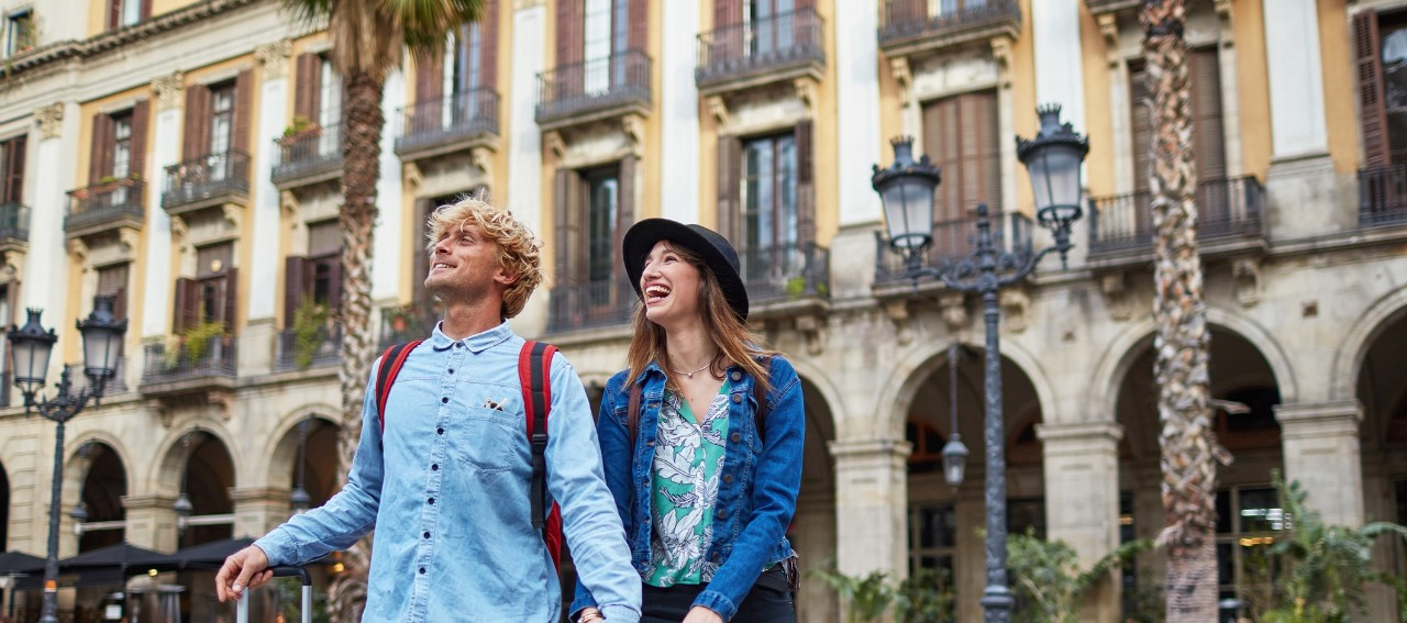 Happy couple holding hands while walking in city. Young male and female tourists are visiting city. Explorers are in casuals on street.