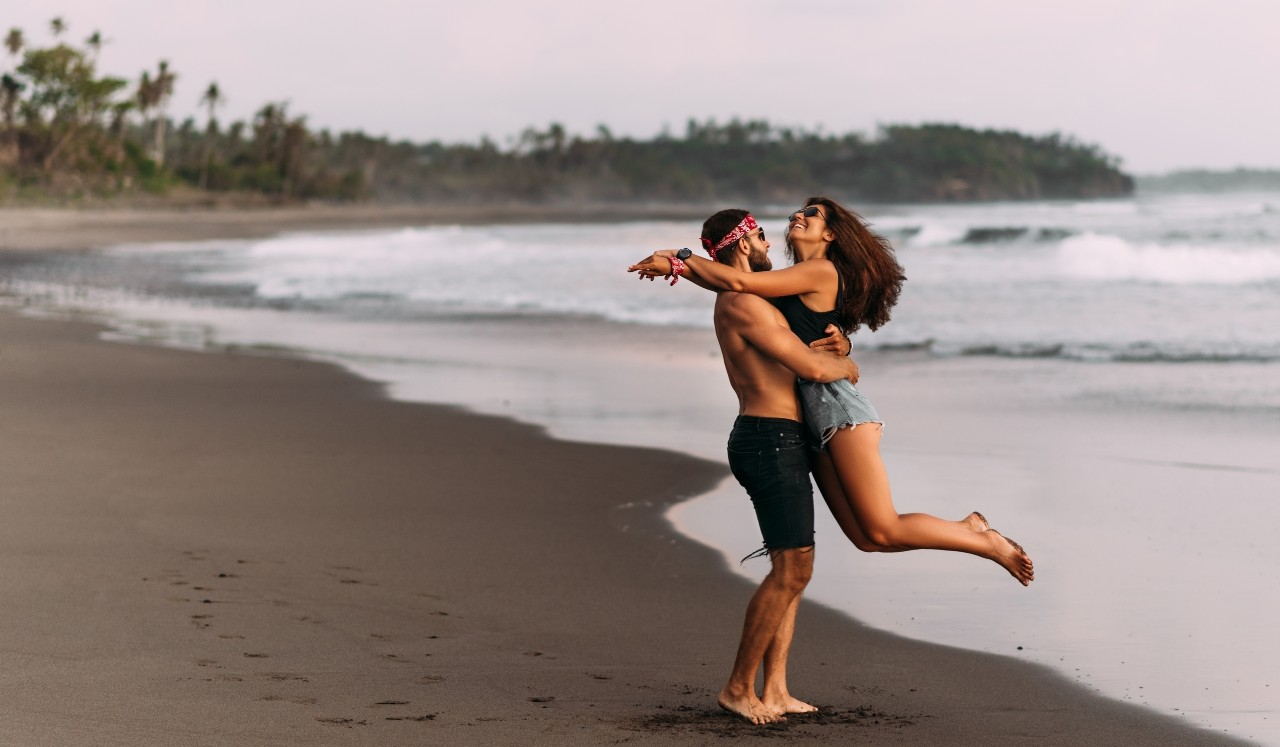 Couple on their honeymoon. Couple travels the world. Happy couple on vacation. Man and woman traveling to Bali. Holidays on beautiful Islands. Lovers meet the sunset on the sea. Happy couple at sunset