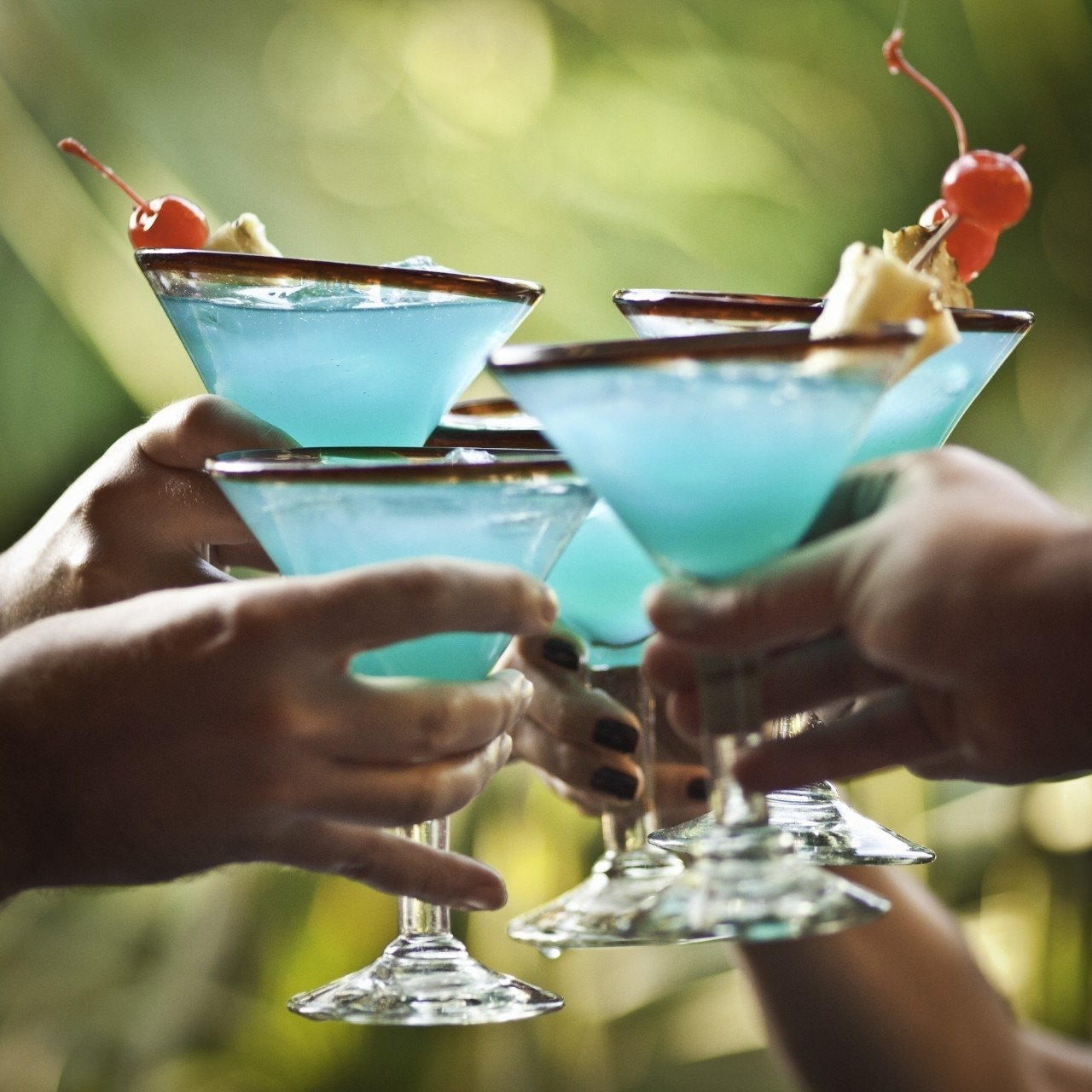 Five friends cheering with Blue Hawaiian drinks.