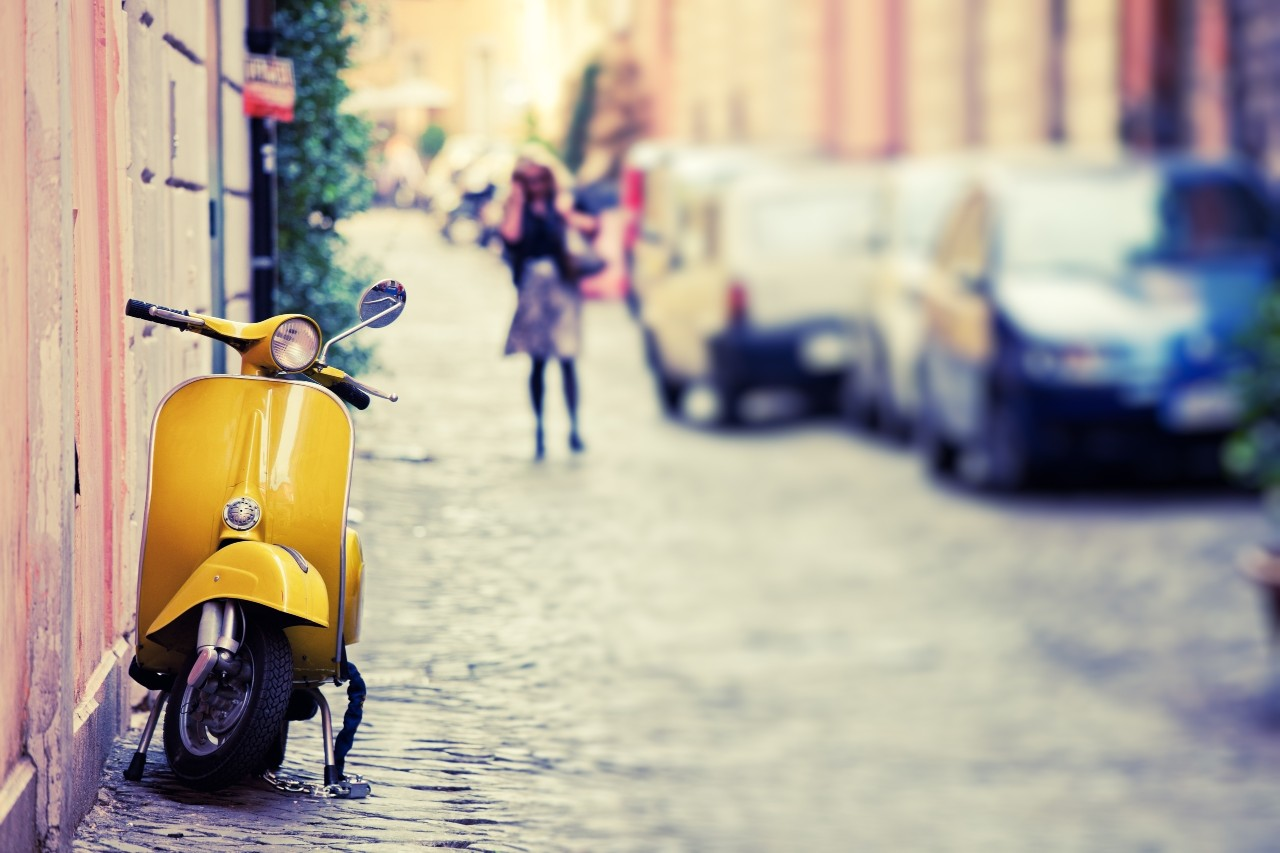 """Italian urban scene with a Vespa, a very typical italian motorcycle, tilt shift lens"""