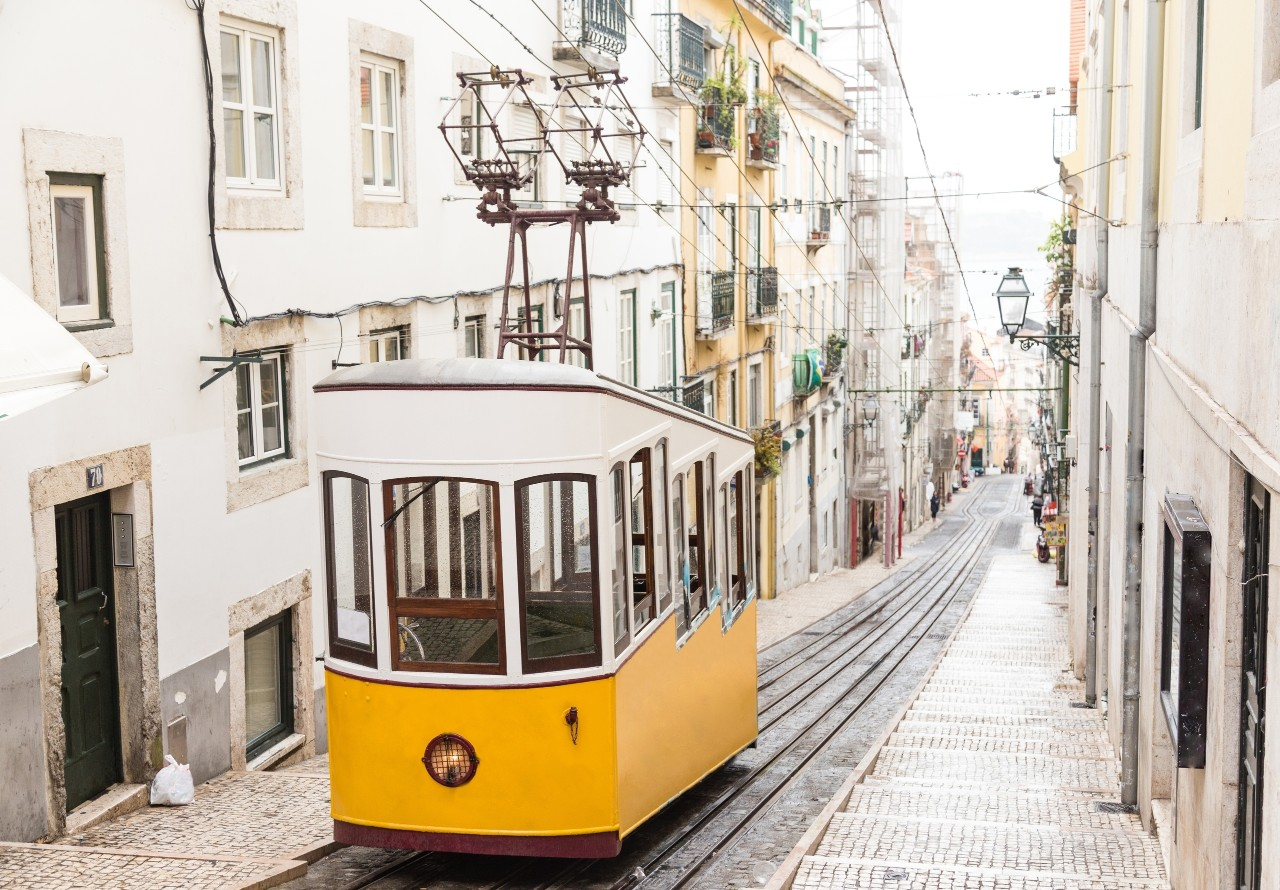 Typical yellow old tram funicular Elevador da Bica in Bairro Alto, going up hill in the old town of Lisbon