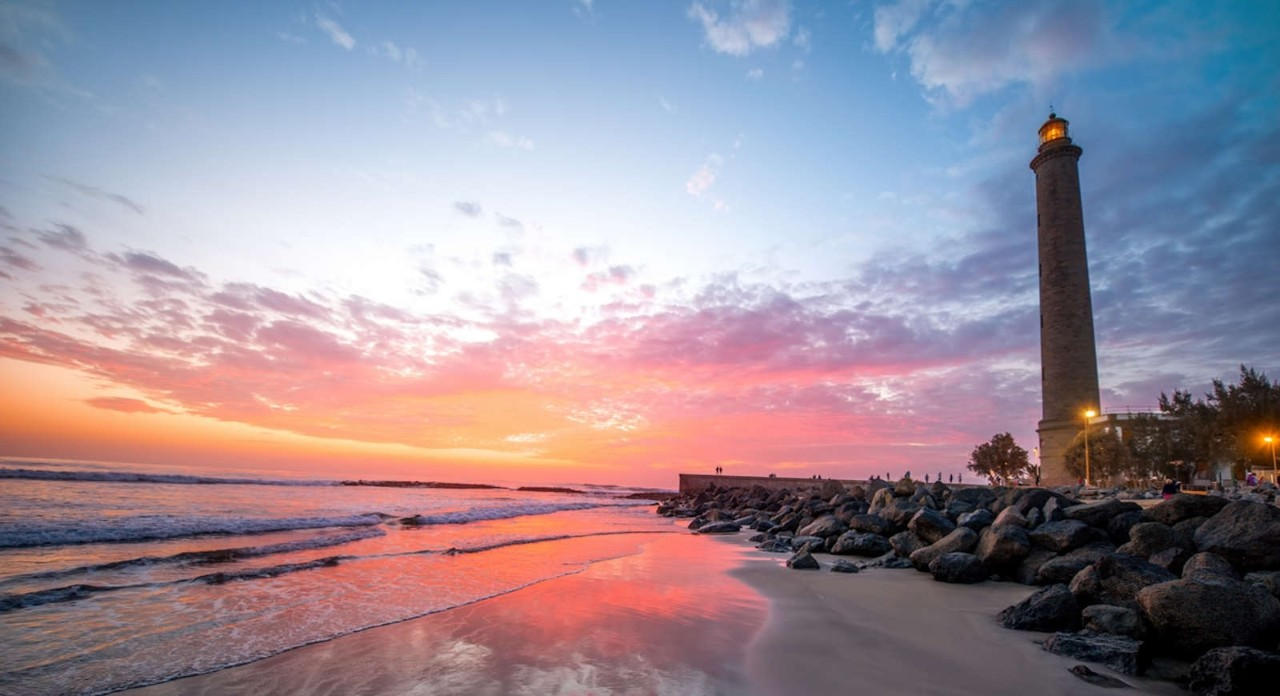 Beautiful sunset view on the beach with lighthouse in Maspalomas city on Gran Canaria island