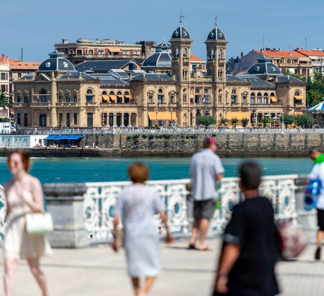 promenade of San Sebastian with city hall and strolling pedestrians in the foreground