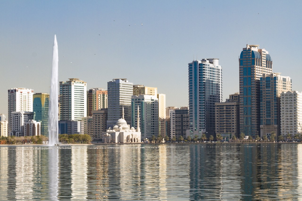 Noor Mosque and jet stream in Khalid Lake, with the city skyline in the background,