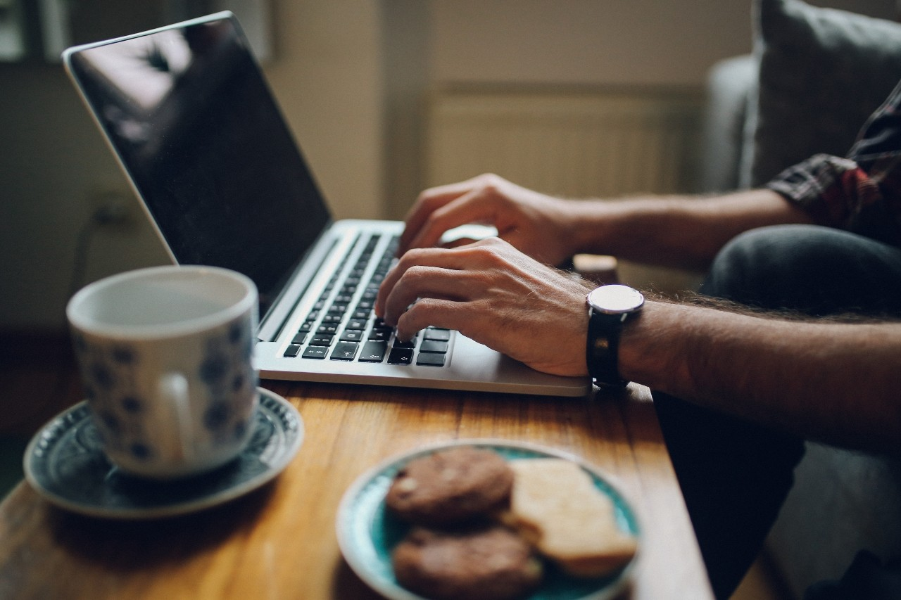 Close up image of a young man's hands typing on the laptop keyboard, and some coffee and sweets set a wooden table in home apartment in Berlin, Germany.