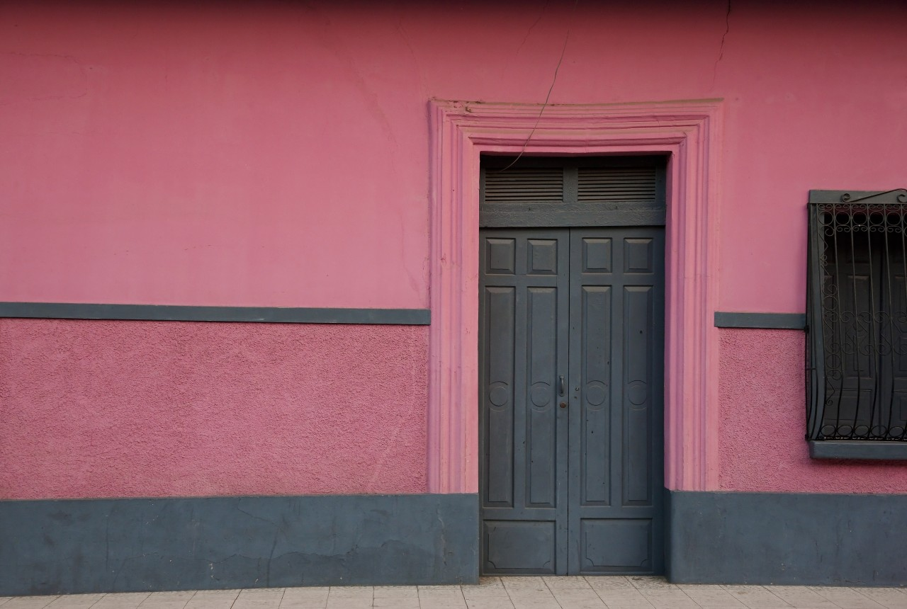 Solid wood old closed door and pink wall in Central America