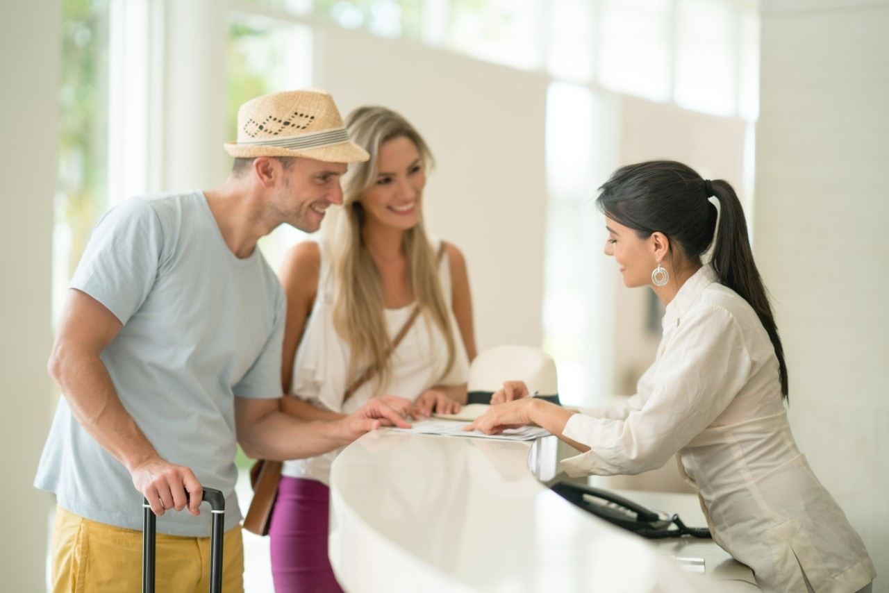 Friendly hotel hostess helping couple with the check-in. People traveling concepts